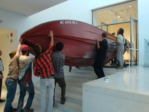 Curators move speedboat into Smart Museum as part of Heartland Exhibit.